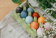 Modern Yellow, Pink, Blue And Grey Easter Eggs Painted With Organic Onion, Beets, Red Cabbage, Carcade Tea. Zero Waste Holiday. Natural Dye Easter Eggs In Carton Tray On Rustic Table With Flowers
