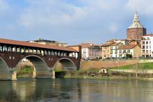 """Pavia, Italy. February14,2018. The Ponte Coperto (""""covered Bridge"""") Or The Ponte Vecchio (""""Old Bridge"""") Is A Brick And Stone Arch Bridge Over The Ticino River In Pavia, Italy. Duomo Di Pavia Visible"""