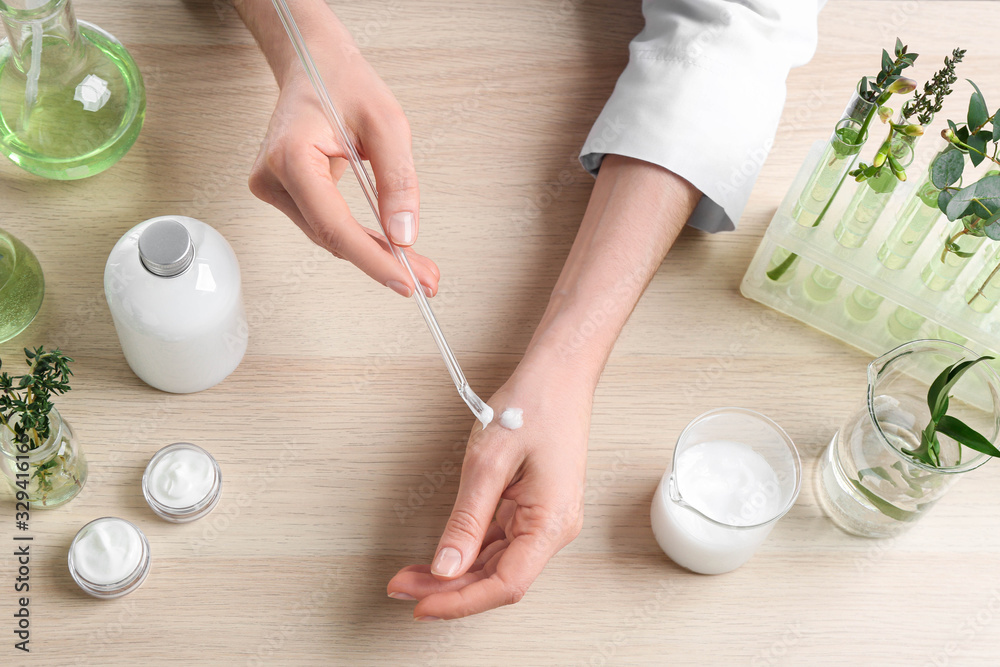 Fototapeta Woman applying natural cream onto hand in cosmetic laboratory, above view