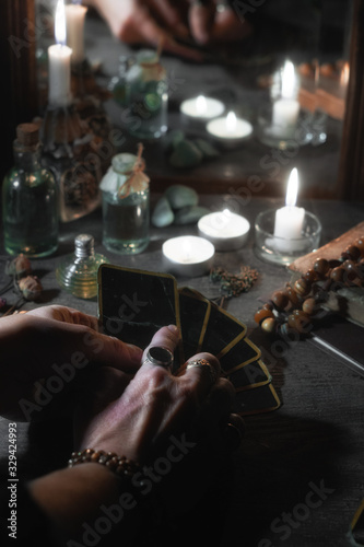 Hands of a sybil with fortunetelling cards and burning candles is reflected in a Billede på lærred