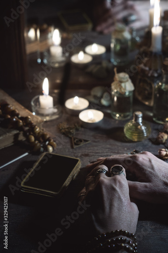 Foto Hands of a sybil with fortunetelling cards and burning candles is reflected in a
