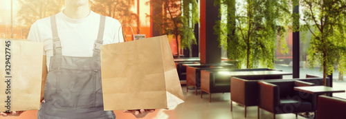 Fototapeta delivery, mail and people concept - happy man delivering food in disposable pape