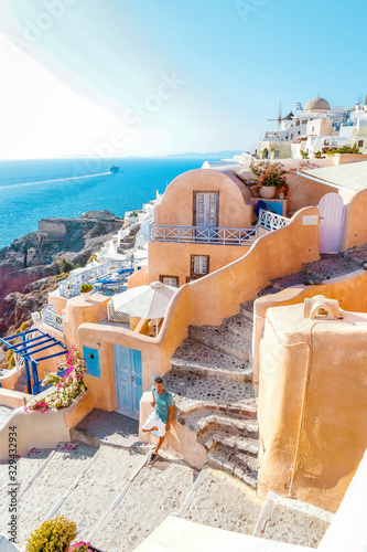 Fototapeta man on vacation Greece visisting Oia Santorini, guy on holiday in Greece on a luxury trip to Oia whitewashed village with Greek churches obraz