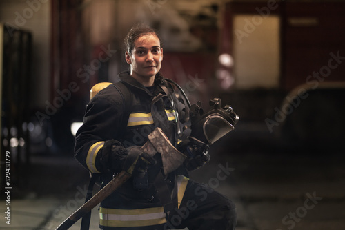 female firefighter portrait wearing full equipment, oxygen mask, and an axe Canvas Print