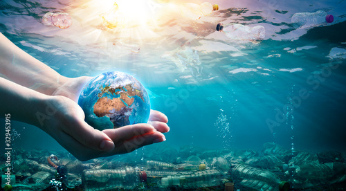 Obraz Plastic Waste In The Environment - Ocean Pollution - Hands Holding Earth - elements of this image furnished by NASA - fototapety do salonu