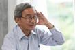 Elder headache illness symptom from wearing glasses.