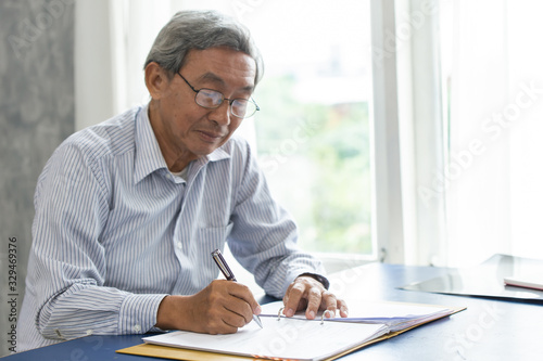Fototapeta Asian smart business elder writing document report in the office. obraz
