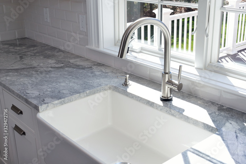Carta da parati Modern kitchen sink and single handle brass faucet with soap dispenser, marble countertop and window to the garden