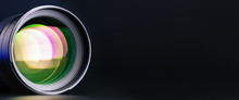 Banner. The Camera Lens With Multi-colored Illumination On A Black Background.  Right Place For Text. Optics.