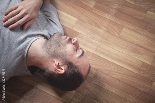Obraz Caucasian unconscious man at home. - fototapety do salonu