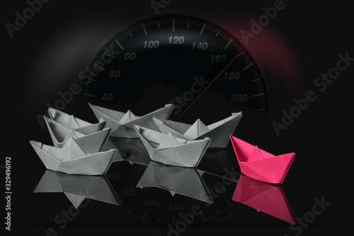 Leadership concept with red paper ship leading among white and speedometer above Canvas Print