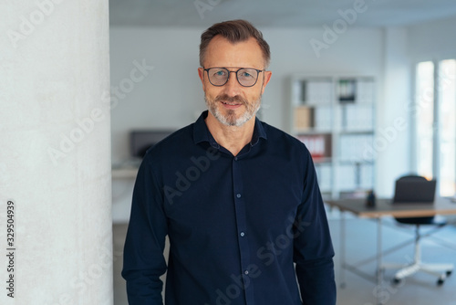 Fototapeta Handsome middle-aged man in glasses in office