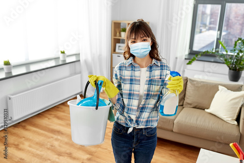 Fototapeta health and hygiene concept - smiling asian woman wearing protective medical mask for protection from virus holding bucket of cleaning stuff and detergent at home obraz