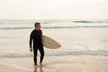 Man Holding Surfboard And Looking At Ocean. Full Length View Of Handsome Middle Aged Surfer In Wetsuit Holding Board And Looking At Waves. Surfing Concept