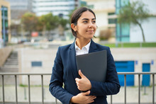 Happy Businesswoman Holding Folder. Smiling Young Businesswoman In Formal Wear Holding Papers And Looking Aside On Street. Professional Occupation Concept
