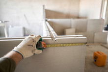 The Construction Worker Measures With A Tape Measure Gypsum Plate. Construction Of Internal Walls In The Apartment Using A Plaster Concrete Plate With Groove Ridge. Tongue-and-groove Gypsum Blocks