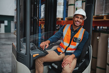 Portrait Of Happy Young African Forklift Manager Wearing Safety Vest And White Hardhat Transporting Goods From One Shelf To Another While Looking In Camera In Warehouse