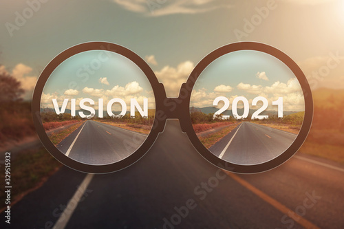 glass magnify against word VISION and 2021 behind the tree of empty asphalt road at golden sunset and beautiful blue sky. Concept for vision new year 2021.