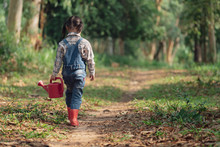 Asian Little Girl Holding Red Watering Tree Walking In Nature. First Learning Of Little Children. Happy Family Concept. Rear View Shot