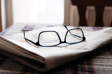 Folded Newspaper And Glasses