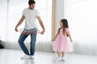I love you, dad! Handsome young man is dancing at home with his little girl. Happy Father's Day!