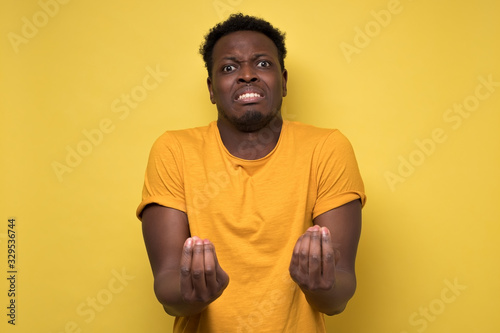 Photo Young handsome african american man showing italian gesture that means what do you want over yellow background