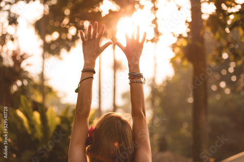 Photo Woman holding hands in the air with orange sunlight in the background