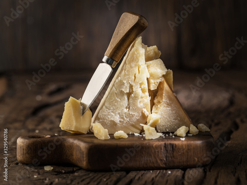 Fototapeta Piece of Parmesan cheese and cheese knife on the wooden board. Dark background. obraz