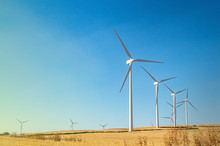 Windmills Wind Turbines Farm Power Generators Against Landscape Against Blue Sky In Beautiful Nature Landscape For Production Of Renewable Green Energy. Friendly Industry To Environment.