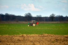 Work In The Field, Old Tractor With Seeder. Spreading Granulated Fertilizer In Spring.
