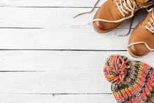 Woman's Winter Shoes And Knitted Hat On White Wooden Background With Copyspace. Top View
