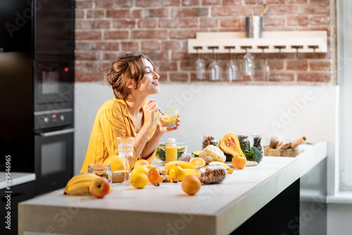 Fototapeta Cheerful woman eating chia pudding at the table full of healthy raw vegetables and fruits on the kitchen at home. Concept of vegetarianism, healthy eating and wellness obraz