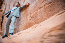 Nervous Businessman Clinging To A Cliff Face While Balancing On A Narrow Ledge In A Red Rock Canyon