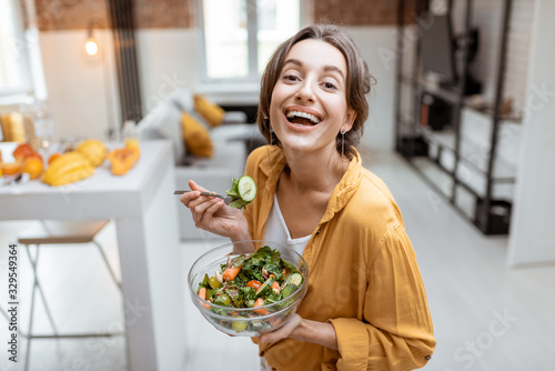 Portrait of a young and cheerful woman dressed in bright shirt eating salad at home. Concept of wellbeing, healthy food and homeliness