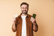 Positive man holding credit card using mobile phone.