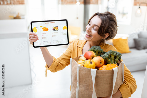Fotografie, Obraz Happy woman holding a digital tablet with launched online store while standing with shopping bag full of fresh products at home