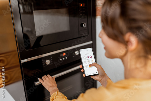 Woman controlling smart kitchen appliance using mobile phone at home, close-up on mobile screen Wallpaper Mural