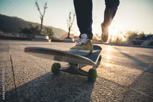 Fotografiet Skateboarder skateboarding at sunrise park