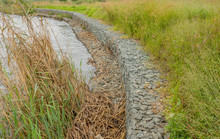 Gabion Retaining Walls To Control Erosion And Flooding On The Banks Of A Fast Flowing River