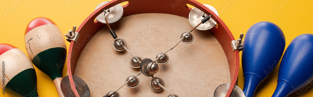 Fotografia Close up view of tambourine near colorful and blue maracas on yellow background,