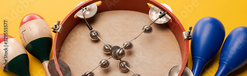 Fotografía Close up view of tambourine near colorful and blue maracas on yellow background,