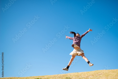 Photographie 両手広げてジャンプする女の子
