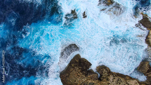 Obraz Wild Ocean water from above - Waves hitting the rocks - aerial photography - fototapety do salonu