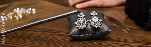 Selective focus of earrings on jewelry pillow near gemstones and hand of jewelry Wallpaper Mural