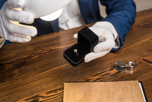Cropped View Of Jewelry Appraiser Holding Ring With Gemstone In Box Near Lamp At Table Isolated On Grey