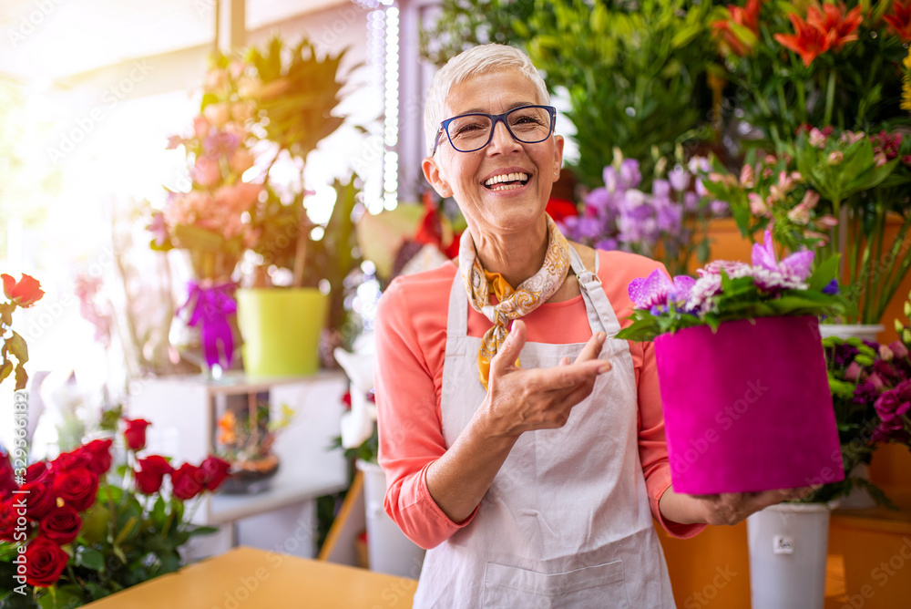Fototapeta Mature smiling florist shop owner surrounded by flowers. Beautiful mature female , smiling works at flower shop. Portrait of mature female florist with flower box looking at camera