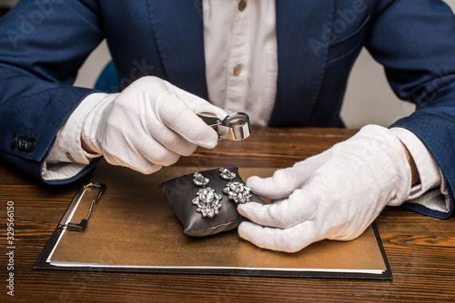 Photo Cropped view of jewelry appraiser holding magnifying glass and earnings on board