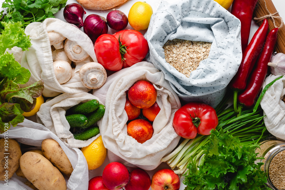 Fototapeta Variety of fresh whole plant food groceries in reusable cotton bags and glass jars. Zero waste vegan groceries concept