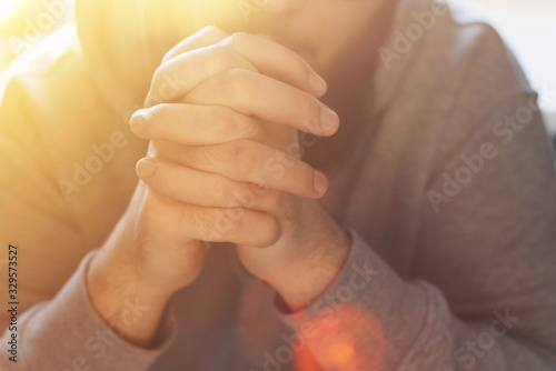 Fotografie, Obraz Bearded adult man praying to God sitting at home in the sunbeam