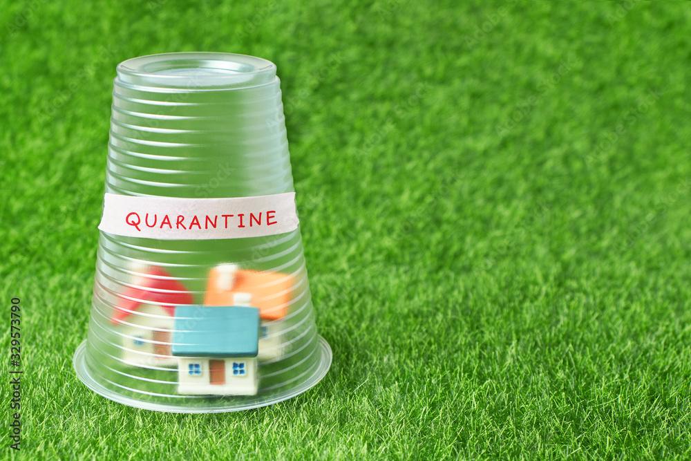 Fototapeta Coronavirus quarantine concept. Small house covered with transparent plastic cup and inscription Quarantine